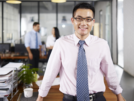 Photo pour asian businessman standing in office happy and smiling with multinational colleagues talking in background. - image libre de droit