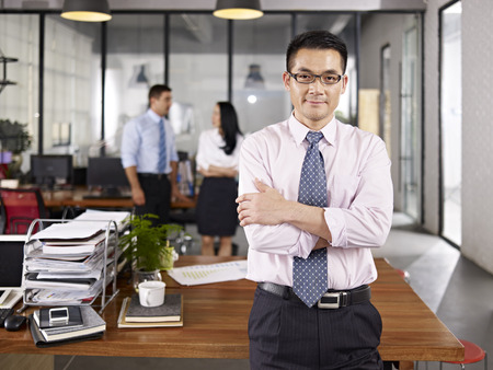 Photo pour asian businessman standing in office arms crossed with multinational colleagues talking in background. - image libre de droit