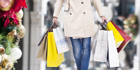 Photo pour woman walking with shopping bags with christmas background. - image libre de droit
