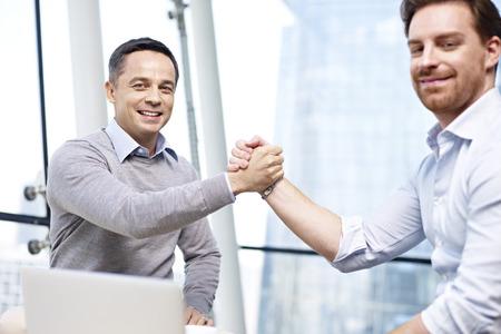 Photo pour two caucasian businesspeople celebrating success in partnership in office. - image libre de droit