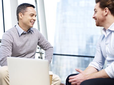 Photo pour two caucasian businessmen chatting during coffee break in office. - image libre de droit