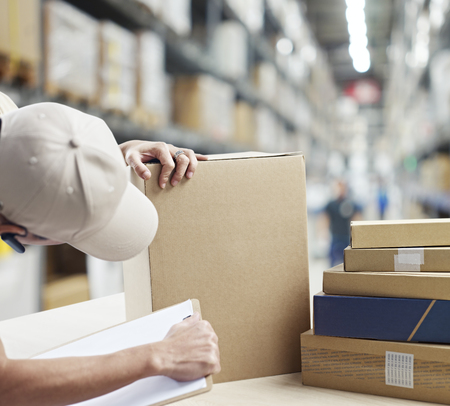 Photo for warehouse worker checking and recording goods received or to be shipped out. - Royalty Free Image