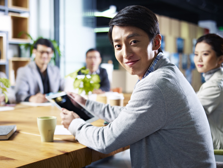 young asian designer business man looking at camera smiling during meeting.
