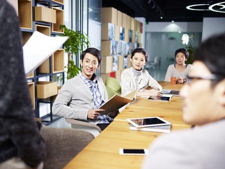 Foto de a team of young asian entrepreneurs meeting in office discussing ideas for new business. - Imagen libre de derechos