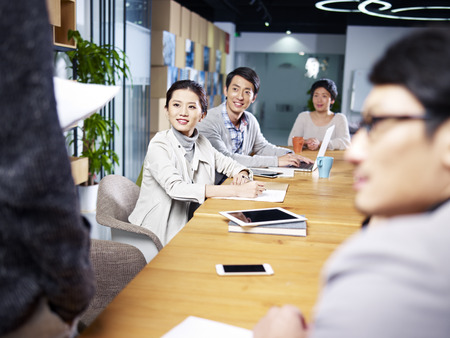 Photo for a team of young asian entrepreneurs meeting in office discussing ideas for new business. - Royalty Free Image