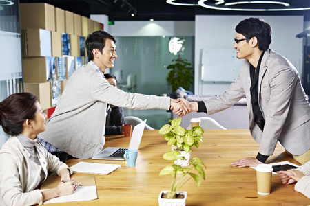 Foto de young asian business people shaking hands smiling before meeting or negotiation - Imagen libre de derechos