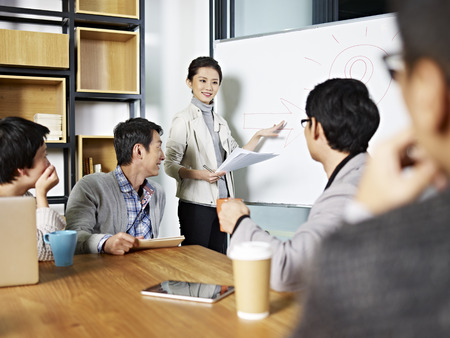 Foto de young asian business executive facilitating a discussion or brainstorm session in meeting room. - Imagen libre de derechos