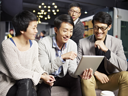 Foto de young asian businesspeople sitting in sofa looking at tablet computer, happy and smiling. - Imagen libre de derechos