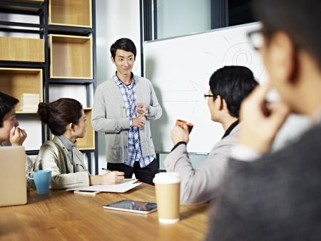 Photo pour young asian businessman facilitating a group discussion or training in office. - image libre de droit