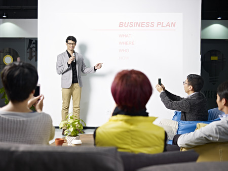 Photo pour young asian entrepreneur presenting business plan for new project with the audience taking picture with cellphones. - image libre de droit
