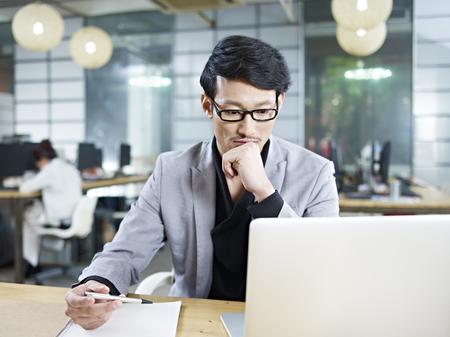 Photo pour young asian business man working in office using laptop computer. - image libre de droit