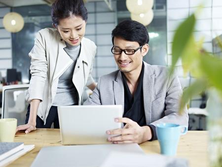 Foto de young asian business people sitting at desk working together using laptop computer. - Imagen libre de derechos