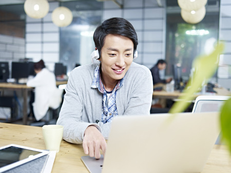 Photo pour young asian businessman sitting at desk in office working using laptop computer while listening to music with headphone. - image libre de droit