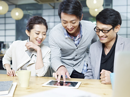 Photo for a team of young asian entrepreneurs discussing business in office using tablet computer. - Royalty Free Image