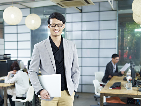 Foto de young asian entrepreneur standing in office with laptop computer under arm. - Imagen libre de derechos
