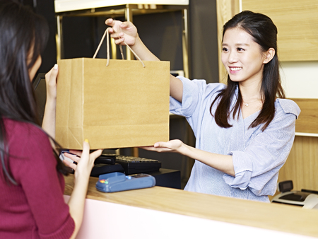 Photo pour young female asian salesclerk handing a paper bag of merchandise to a customer at the check-out counter - image libre de droit