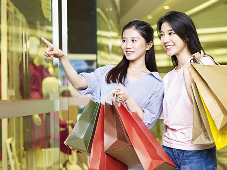 Foto de two beautiful young asian woman shopping in mall or department store - Imagen libre de derechos