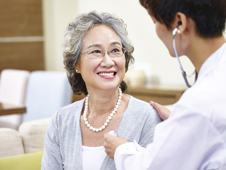 Photo for family doctor checking smiling senior asian woman using stethoscope - Royalty Free Image