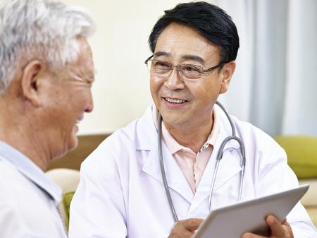 Photo pour asian doctor talking to a senior patient, happy and smiling - image libre de droit