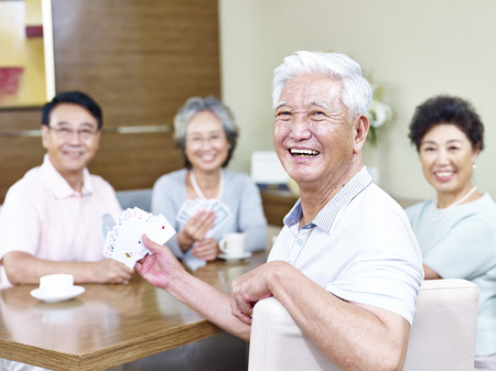 Photo pour senior asian man looking at camera smiling while playing cards with friends. - image libre de droit