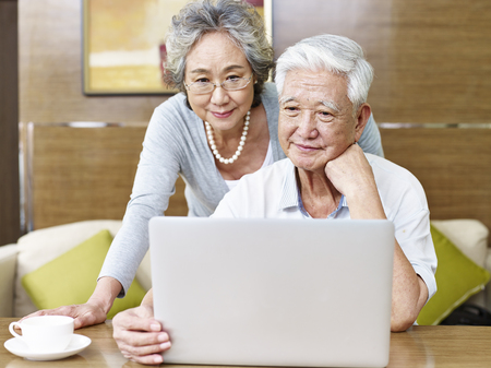 Photo for loving senior asian couple using a laptop computer together. - Royalty Free Image