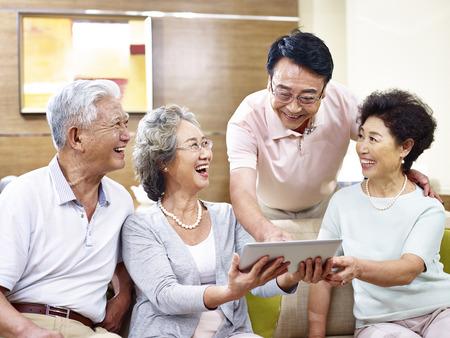 Photo pour senior asian couples having a good time using tablet computer together. - image libre de droit