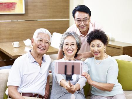 Photo pour two happy senior asian couples taking a selfie using cellphone on a stick. - image libre de droit