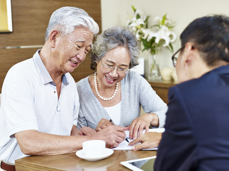 Foto de happy senior asian couple signing a contract agreement in front a salesperson. - Imagen libre de derechos