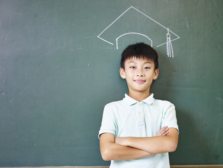 Photo for asian elementary school boy standing under a doctoral hat drawn with chalk on blackboard. - Royalty Free Image