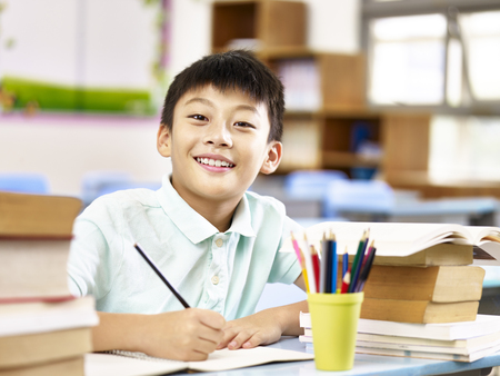 Photo pour asian primary school student looking at camera smiling while studying in classroom. - image libre de droit