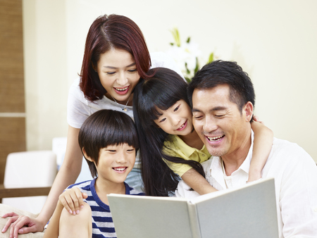 Foto de happy asian family with two children sitting on sofa reading a book together. - Imagen libre de derechos