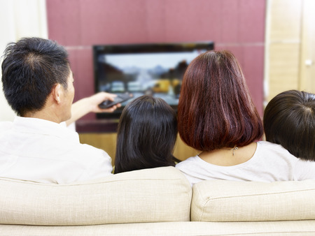 Foto de asian family sitting on couch at home watching TV, rear view. - Imagen libre de derechos