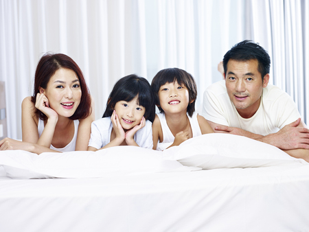 Photo pour happy asian family with two children lying on front in bed looking at camera smiling. - image libre de droit