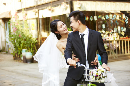 Photo for romantic asian newly wed couple having fun riding a bicycle together. - Royalty Free Image