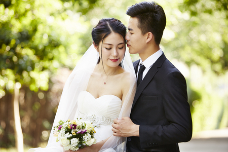 Photo pour young asian groom kissing bride outdoors during wedding ceremony. - image libre de droit