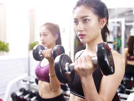 Foto de two young asian women working out exercising in gym using dumbbells. - Imagen libre de derechos