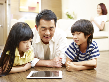 Photo for asian mother and two children lying on front on floor playing with digital tablet while mother watching in the background. - Royalty Free Image