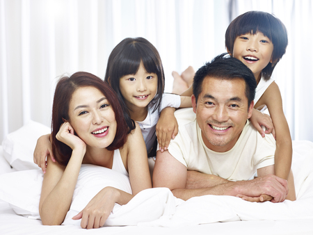 Photo for happy asian family with two children having fun in bed at home. - Royalty Free Image