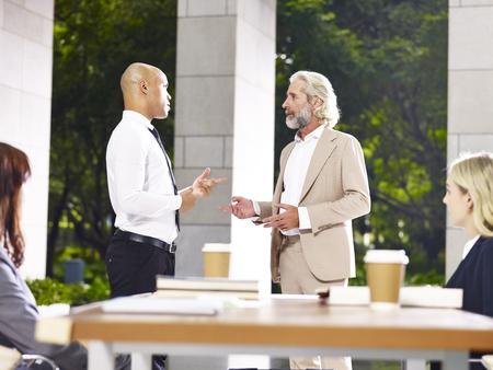 caucasian and latino corporate business executives  debating during meeting