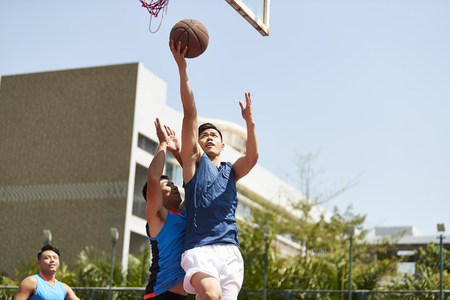 Foto de young asian basketball player going up for a layup while opponent playing defense. - Imagen libre de derechos