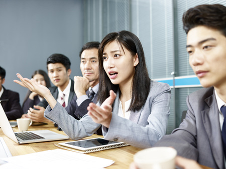 Photo pour young asian business woman executive engaging in a heated discussion during meeting. - image libre de droit