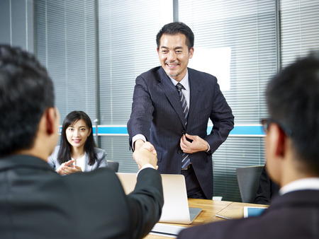 Photo for two asian business men shaking hands over meeting table before negotiation. - Royalty Free Image