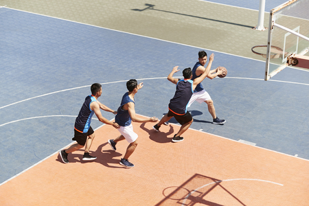 Photo pour young asian male basketball players playing a game on outdoor court. - image libre de droit