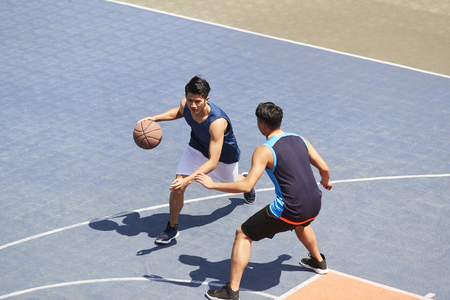 Photo for two young asian basketball players playing one on one on outdoor court. - Royalty Free Image