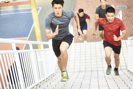 young asian men training running on steps outdoors