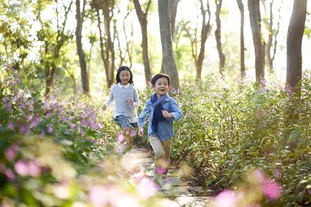 Foto de two little asian children boy and girl running through field of flowers in park. - Imagen libre de derechos