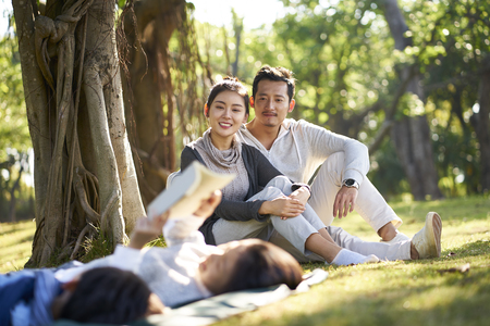 Photo pour two asian children little boy and girl having fun lying on grass reading a book with parents sitting watching in background. - image libre de droit