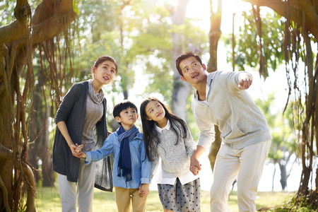 Foto de asian family with two children having fun exploring woods in a park. - Imagen libre de derechos