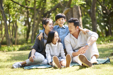 asian family with two children having fun sitting on grass talking chatting outdoors in park
