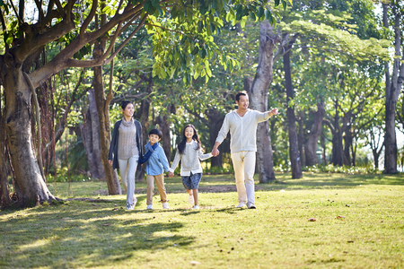Photo pour asian family with two children walking hand in hand outdoors in park. - image libre de droit